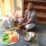 Volunteer Venkat Rao dressing vegetables for evening food.