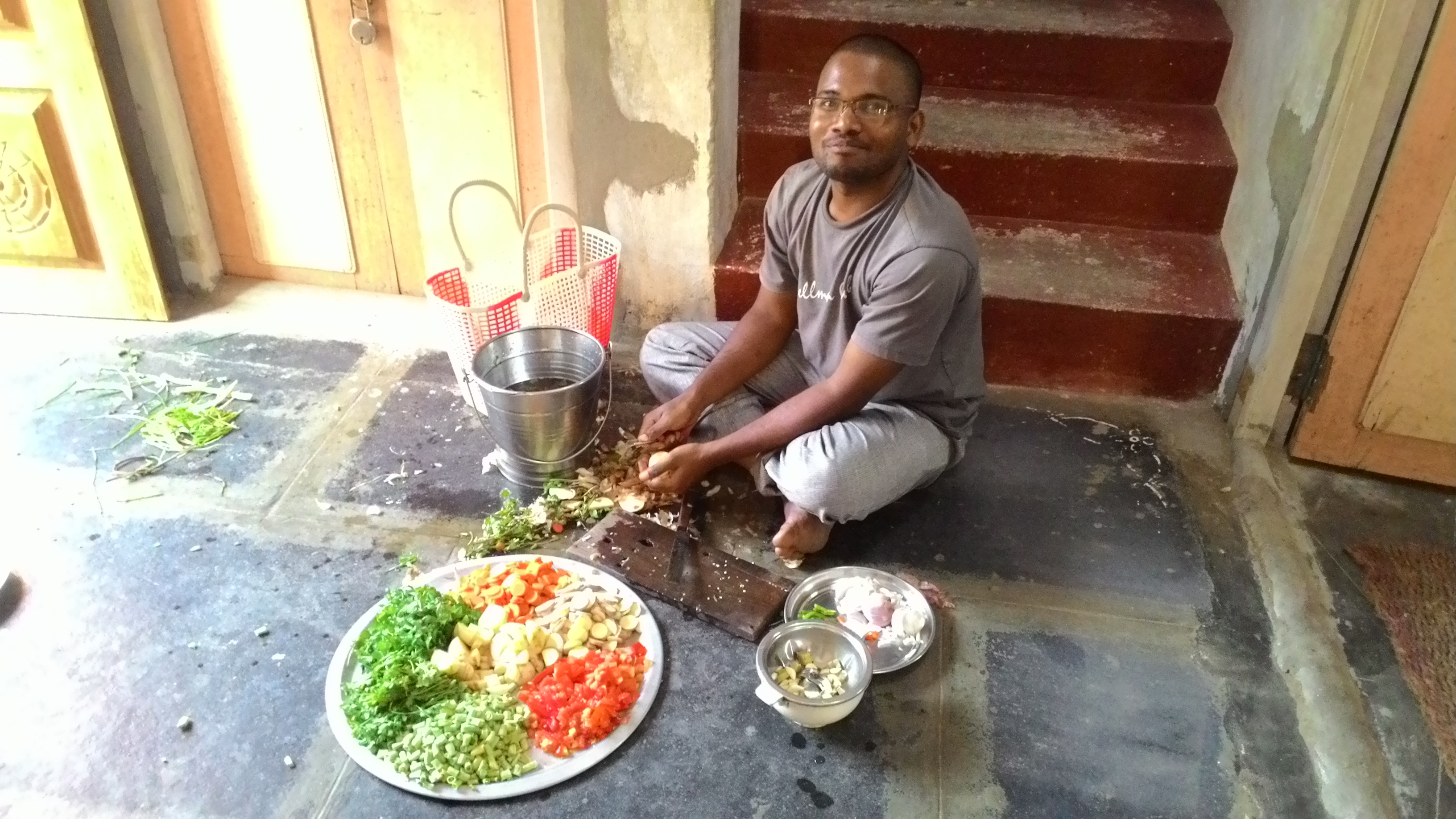 Volunteer Venkat Rao dressing vegetables for evening food.