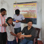 C Sridhar IAS giving away the monthly toiletries etc.